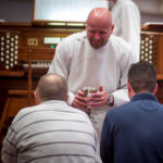 A worship assistant administers communion