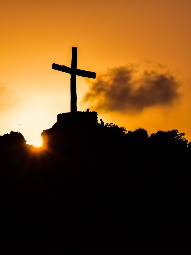 Cross on a hill silhouetted against the sunset